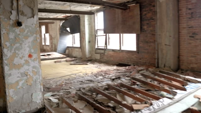 POV: Paint peeling from demolished weathered walls in abandoned house in ruins video
