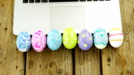 Painted Easter eggs and laptop on wooden surface video