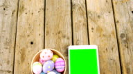 Painted Easter eggs in a bowl and digital tablet on wooden surface video