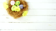 Painted Easter eggs in the nest on wooden surface video