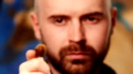 Painter holding paintbrush, portrait background, close up, dynamic change of focus, slow motion video