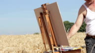 painter in the middle of a wheat field paints a beautiful landscape, PAN video