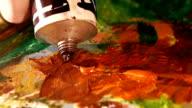 Painter squeezes brown oil paint on a palette, close up, slow motion video