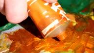 Painter squeezes orange oil paint on a palette, close up, slow motion video