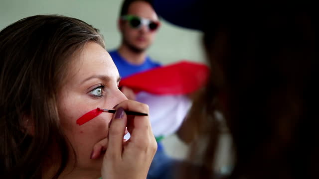 Painting face to sport supporter for the championship video