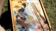 Painting outdoors. Artist working en plein air video