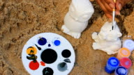 painting toy with difference color on the beach video