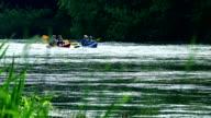 pair canoe kayak racing sports on wild water river through reeds. video