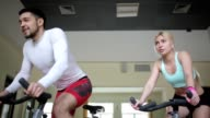 Pair of athletes accelerating on exercise bikes video