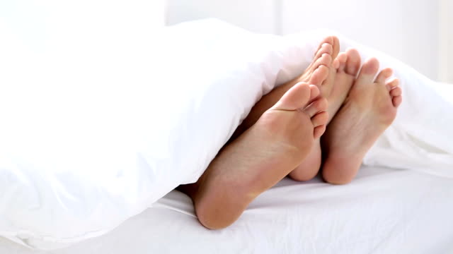 Pair of feet playing footsie under the covers video