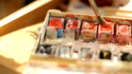 Palette and brush. Red watercolor. Brush dipped in water colors video