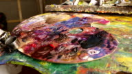 A palette with paints in an art workshop video