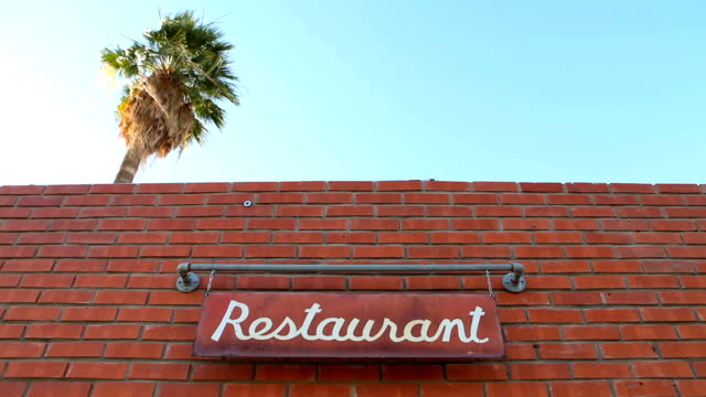 Palm Tree Towers Over a Restaurant as a Sign Swings video