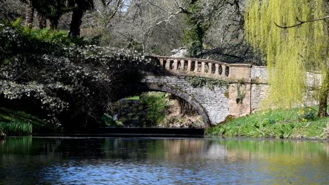 Pan across lake to old bridge in English countryside video