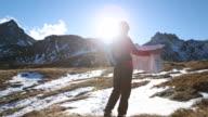 Pan as hiker checks map by mountain range, sunrise video