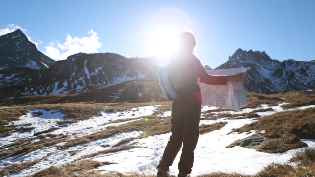Pan as hiker checks map by mountain range, sunrise video
