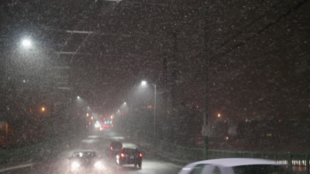Pan Down to Cars Driving at Night in Dangerous Bad Weather with Thick Snow Flakes video