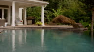 Pan of a beautiful pool and poolhouse in the mountains, in slow motion video