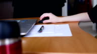 Pan shot of woman using mouse and typing keyboard at home video