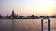 Pan shot Wat Arun at Sunset, Temple of the Dawn in Bangkok, Thailand, Chao Phraya River. twilight moment of famous skyline video