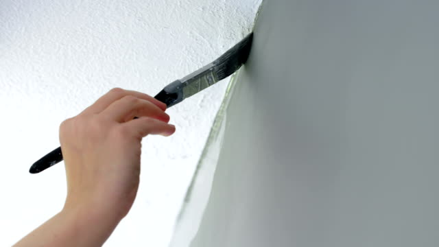 Pan to follow painting top edge of gray wall with a brush video