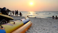 panning: lifestyle of people in summer behind banana boat on the beach video