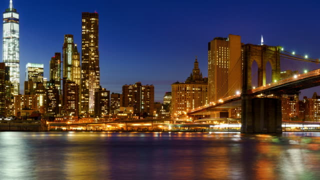 Panning of Lower Manhattan Financial District skyscrapers at twilight with the Brooklyn Bridge. New York City video