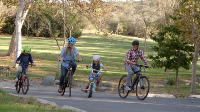 Panning shot following family cycling together in a park video
