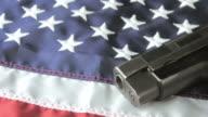 Panning Shot of a Handgun Lying on an American Flag video