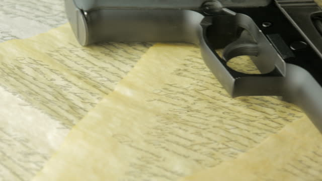 Panning Shot of a Handgun Lying on the United States Constitution video