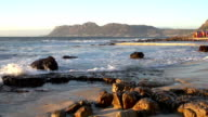 Panning shot of brightly coloured changing rooms and tidal pool,St. James beach,Cape Town video