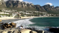Panning shot of Camps Bay beach with mother and child enjoying the view, video