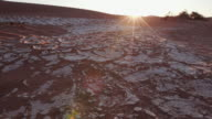 4K panning shot of dry cracked mud with sun setting in the background inside the Namib-Naukluft National Park video