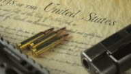 Panning Shot of Multiple Firearms and Ammunition Lying on the US Constitution video