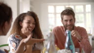 Panning shot of young adult friends talking at dining table video