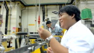 panning: young engineers using twin screw extruder machine video