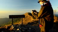 Panning: Young man  Capturing Memories With Phone  on peak of mountain video