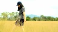 panning: young woman carefully walk  on Savannah field video
