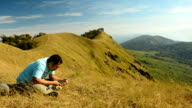 panning:two men relax at the peak of a mountain in Thailand video