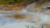 panorama of geothermal area Krysuvik in Iceland with bright blue hot mud, white steam is over area video