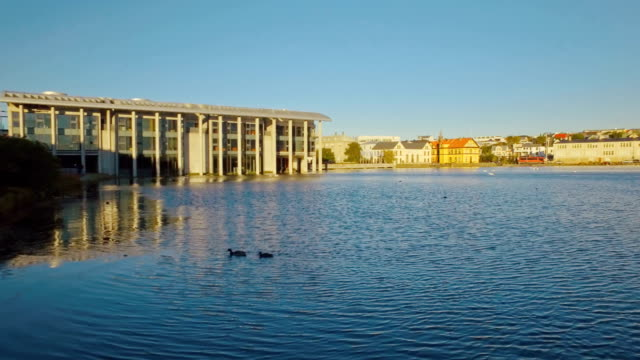 panorama of lake Tjornin in centre of Reykjavik in Iceland with parliament building, sunny video