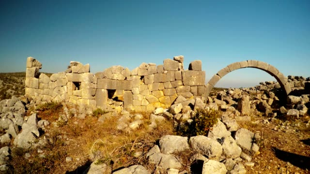 Panorama The most extant build with polygonal laying and arches among ruins blue sky Adamkayalar Mersin province Turkey video