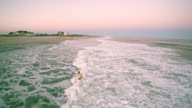 Panoramic low altitude aerial view toward the Hampton Beach from the ocean, with the young man swimming in the ocean. video