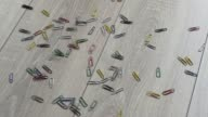 Paperclip spilled on a beautiful wooden floor. Falling small colored paperclip backlit. Reverse. video