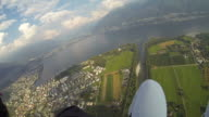 POV paraglider flying over river next to town video