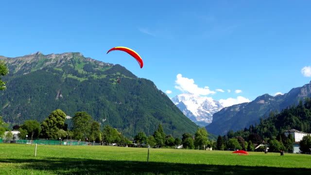 INTERLAKEN, SWITZERLAND: Paragliders in front of the Alps in Interlaken, Switzerland. Interlaken is a resort town in the Interlaken-Oberhasli administrative district in the Swiss canton of Bern. video