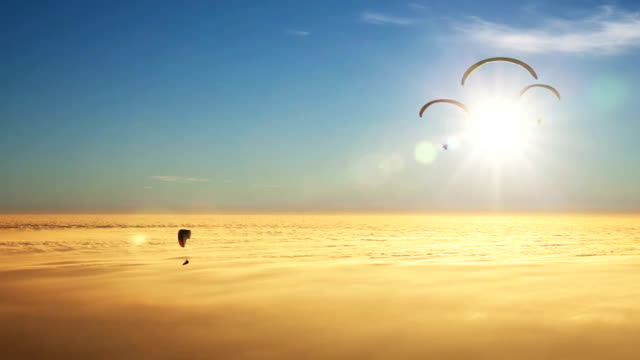 Paragliders on a sea of golden clouds with sun video