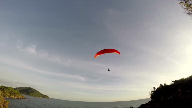 Paragliding over the mountains against clear blue sky video