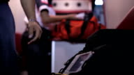 Paramedics preparing equipment in ambulance video