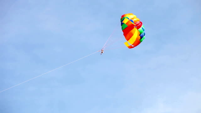 Parasailing under a cheerful rainbow colored parachute video